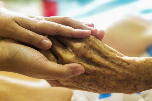 患者さんの手を握る看護師さんの手